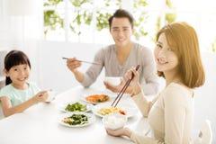 Счастливая молодая семья наслаждается их обедающим Стоковые Фотографии RF