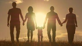 Счастливая молодая семья при дети бежать вокруг поля, силуэта на заходе солнца Стоковое фото RF