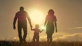 Счастливая молодая семья при дети бежать вокруг поля, силуэта на заходе солнца сток-видео