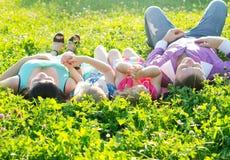 Счастливая молодая семья при дети лежа на траве в sunsh стоковые изображения