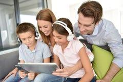 Счастливая молодая семья сидя на софе и используя таблетку Стоковое Изображение