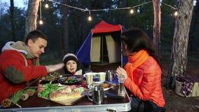 Счастливая молодая семья сидя на таблице и беседе, лесе осени акции видеоматериалы