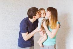 Счастливая молодая семья с младенцем indoors Стоковые Фото