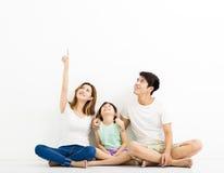 Счастливая молодая семья указывая и смотря вверх Стоковые Изображения RF