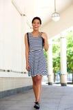 Счастливая молодая чернокожая женщина в striped платье идя снаружи Стоковые Изображения RF