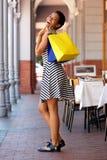 Счастливая молодая чернокожая женщина в striped платье идя с хозяйственными сумками Стоковое Фото
