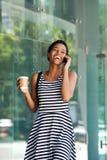 Счастливая молодая чернокожая женщина идя и говоря на мобильном телефоне Стоковые Фотографии RF