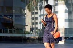 Счастливая молодая чернокожая женщина смотря мобильный телефон и слушая к музыке Стоковые Изображения