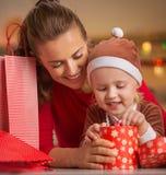 Счастливая молодые мать и младенец проверяя приобретения рождества Стоковое Изображение
