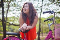 Счастливая наварная женщина представляя с велосипедом стоковое фото rf