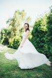 Счастливая невеста закручивая вокруг с вуалью стоковые фото