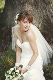 Счастливая невеста представляя в саде. Стоковая Фотография