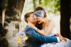 Счастливая невеста, groom стоя в зеленом парке, целующ, усмехающся, смеясь над любовники в дне свадьбы Стоковые Изображения