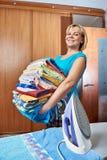 Счастливая домохозяйка с большим стогом полотенец стоковая фотография rf