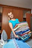 Счастливая домохозяйка с большим стогом полотенец стоковое фото