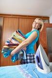 Счастливая домохозяйка с большим стогом полотенец стоковые изображения