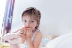 Счастливая дочь девушки есть ее ногу смотря камеру на родительской кровати ` s на утре Счастливая расслабленная семейная жизнь с Стоковые Фото