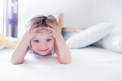 Счастливая дочь девушки усмехаясь и делая смотрит на смотреть камеру на родительской кровати ` s на утре Счастливая расслабленная Стоковое Изображение RF