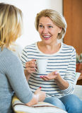 Счастливая дочь деля сплетни с зрелой мамой пока чай-drinkin Стоковые Изображения RF