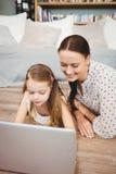 Счастливая дочь используя компьтер-книжку с матерью пока лежащ на паркете Стоковые Изображения RF