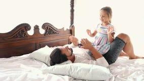 Счастливая дочь маленького ребенка идиллии семьи скачет на оружия отца и они падает на кровать сток-видео