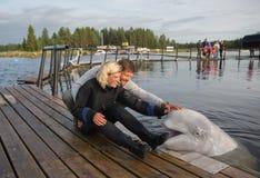 Счастливая пара ласкать белого кита стоковая фотография rf