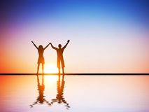Счастливая пара в влюбленности вместе с поднятыми руками стоковое изображение rf