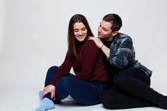 Счастливая пара ослабляя на белом поле Красивый парень нося проверенную рубашку касаясь его милой подруге одел в джинсах и r стоковая фотография rf
