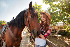 Счастливая пастушка женщины позаботить о ее лошадь на ферме Стоковая Фотография
