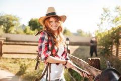 Счастливая пастушка женщины подготавливая седловину для верховой лошади Стоковое Фото