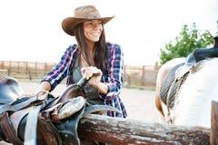 Счастливая пастушка женщины усмехаясь и подготавливая седловину для верховой лошади Стоковые Фотографии RF