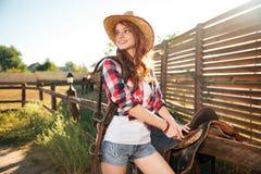 Счастливая пастушка женщины redhead подготавливая седловину для верховой лошади Стоковое Фото
