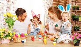 Счастливая пасха! мать, отец и дети семьи красят яичка для стоковое фото