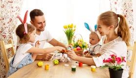Счастливая пасха! мать, отец и дети семьи красят яичка для стоковые изображения