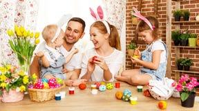 Счастливая пасха! мать, отец и дети семьи красят яичка для стоковое изображение