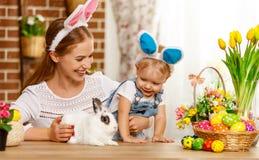 Счастливая пасха! мать семьи и сын младенца играя с кроликом a стоковые фото