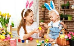 Счастливая пасха! мать семьи и сын младенца красят яичка на праздник стоковая фотография rf