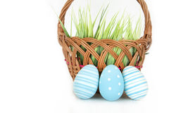 Счастливая пасха - немногие яичка на деревянной корзине с травой на белой предпосылке Стоковые Изображения RF