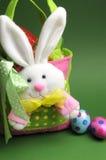 Охота пасхального яйца с цветастым зайчиком многоточия польки носит мешок корзины Стоковые Фото