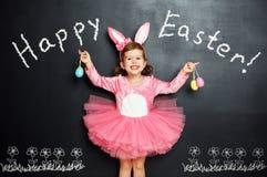 Счастливая пасха! Ребенок с ушами и яичками зайчика Стоковое Изображение