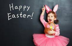 Счастливая пасха! Ребенок с ушами и яичками зайчика Стоковые Изображения