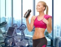 Счастливая питьевая вода женщины от бутылки в спортзале Стоковое Изображение
