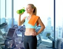 Счастливая питьевая вода женщины от бутылки в спортзале Стоковое Фото