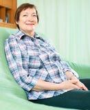 Счастливая пожилая женщина в вскользь одеждах сидя на софе Стоковая Фотография