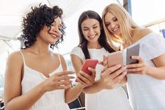Счастливая положительная женщина держа их smartphones Стоковые Изображения RF