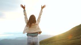 Счастливая празднуя выигрывая женщина успеха на заходе солнца или восходе солнца стоя ликующа с оружиями подняла вверх над ее гол