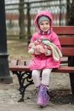 Счастливая прелестная девушка ребенка в розовом пальто при клобук сидя на парке города весны стенда весной Стоковое Изображение RF