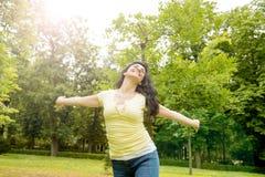 Счастливая привлекательная латинская женщина бросая ее руки в воздухе ослабляет стоковые фото