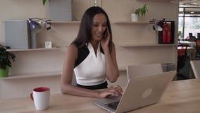 Счастливая профессиональная коммерсантка говоря на smartphone и дает клиента совета видеоматериал