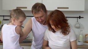 Счастливая дружная семья играет о варя завтрак в кухне Вся семья делает завтрак в кухне сток-видео